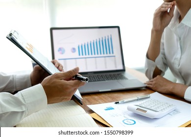 young business team in casual style have small meeting in the office talk about  analyses chart graph marketing plan with computer laptop calculator.