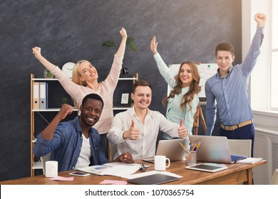 Young business team enjoying success, looking at computer screen, celebrating successful project, dealing contract, winning tender, copy space