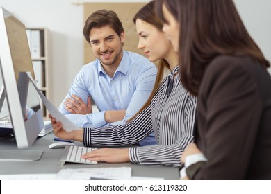 Young business team having a meeting grouped around a computer reading a document with focus to a smiling man