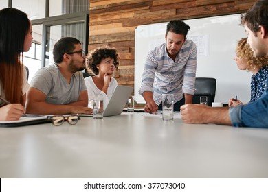 Young business team in a meeting discussing progress of the company. Creative professionals sitting around a table in office.