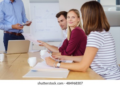 Young business team in a meeting seated around a table in the office with focus to a smiling businesswoman listening to a colleague