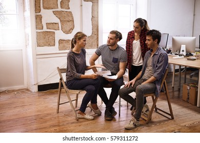 Young business team sitting in a semi circle sharing fresh ideas while everyone is looking at the lady explaining something to them