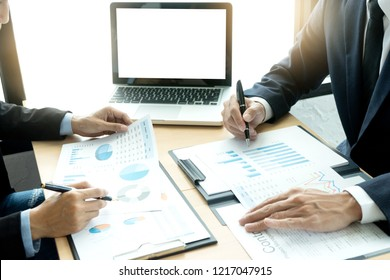 young business team in a small meeting in the office talk about  analyses chart graphy marketing plan with computer laptop. with white computer screen with clipping path