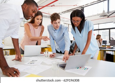 Young business team work standing at desk in a busy office