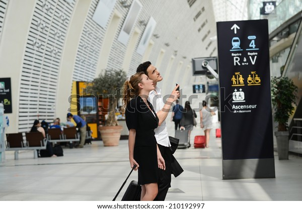 young business travelers man and woman in public transportation station looking for information and schedule