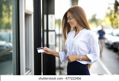 Young business woman in the ATM.