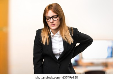Young business woman with back pain on unfocused background