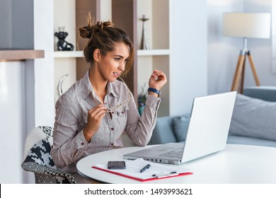 Young business woman biting eyeglasses and looking at her laptop.