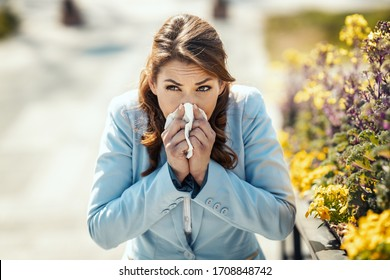 A young business woman blowing her nose out during a break outside due to allergies or colds.