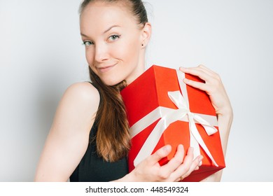 young business woman with a box gift isolated on a gray background