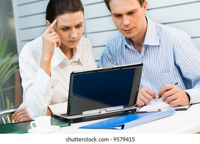 Young business woman and businessman looking at the monitor of laptop placed on the table