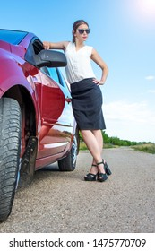 young business woman with car. Sexy rich fashion girl posing near red car on road.