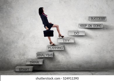 Young business woman carrying a briefcase and climbing a ladder with strategy texts toward success