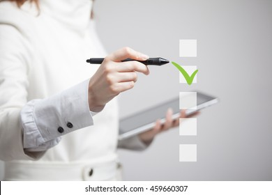 Young business woman checking on checklist box. Gray background.