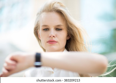 Young business woman checking the time on her watch.