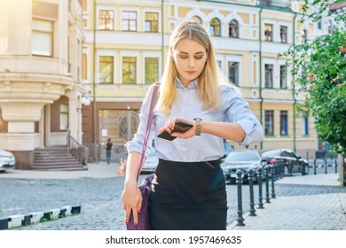 Young business woman in city looking at her wristwatch