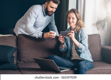 Young business woman in denim jacket sitting on couch in room and shows bearded businessman pictures on smartphone screen.Nearby is laptop, man holding cup of coffee.Friends shopping online, chatting.