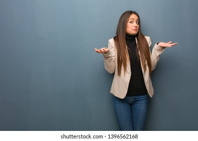 Young business woman doubting and shrugging shoulders