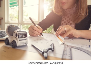 Young Business Woman Drawing Blueprint At Office Desk.