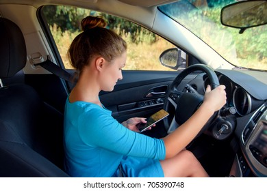 Young business woman in dress looking to smartphone screen while driving car. Young female driver using touch screen smartphone and gps navigation in car. Reading or texting SMS while driving car