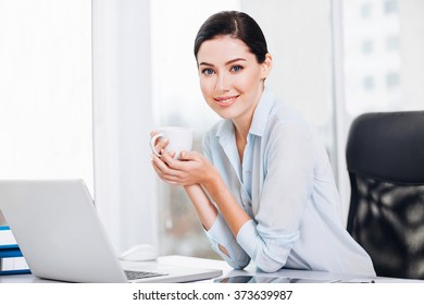 Young business woman drinking coffee and using laptop at office