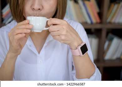 Young Business woman drinking hot coffee. female model holding mug cup in her hand. Close Up. Focus on the arm.