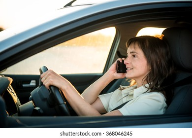 Young business woman driving car and calling phone