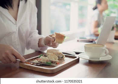 Young business woman eating burger with coffee at the workplace in office