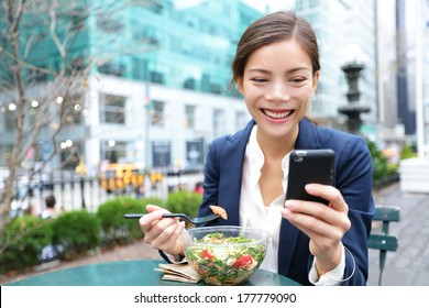 Young business woman eating salad on lunch break in City Park living healthy lifestyle working on smart phone. Happy smiling multiracial young businesswoman, Bryant Park, manhattan, New York City, USA