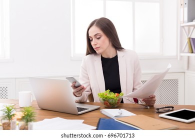Young business woman eating salad at office, having healthy lunch at workplace while using phone and reading papers