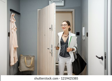 Young business woman entering the apartment returning from the work to home