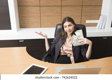 A young business woman feeling comfortable, holding the money, and working with tablet and computer.