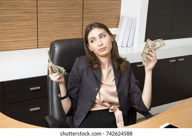 A young business woman feeling stressed, holding the money, and working in the office.