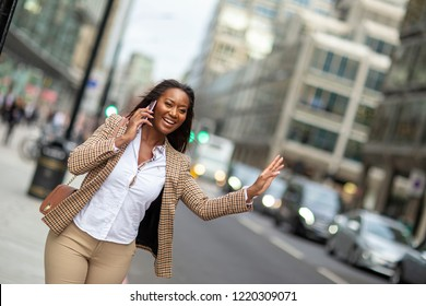 A young business woman flagging down a taxy while on the phone