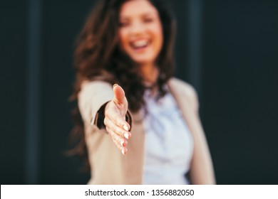 Young business woman gives a hand for handshake outdoor selective focus on hand
