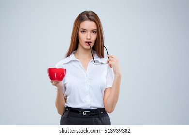 The young business woman in glasses with red cup of coffee on a gray background