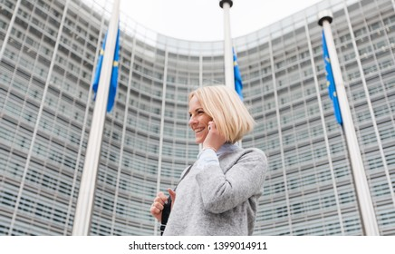 Young business woman goes with the phone in her hands near the European Commission in Brussels, Belgium