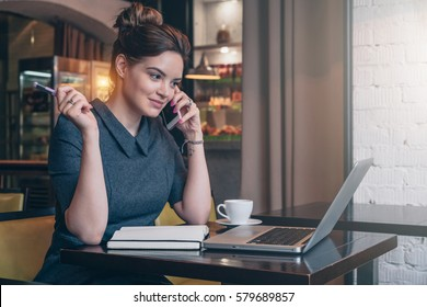 Young business woman in gray dress sitting at table in cafe, talking on cell phone while looking on screen of laptop. On table notebook and cup of coffee. Freelancer working. Student learning online.
