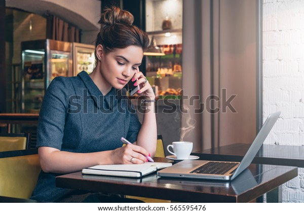Young business woman in gray dress sitting at table in cafe, talking oncell phone while taking notes in notebook. On table laptop and cup of coffee. Student learning online. Freelancer working online.