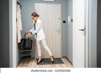 Young business woman at the hall of the apartment returning after the job