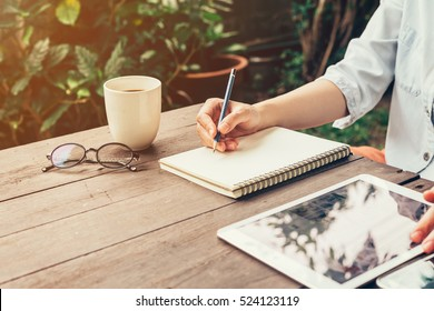 Young business woman hand with pencil writing notebook with phone and tablet on wood table in coffee shop.