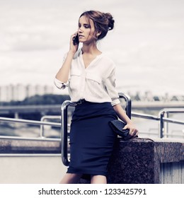 Young business woman with handbag calling on cell phone in city street Stylish fashion model wearing white shirt and black pencil skirt outdoor