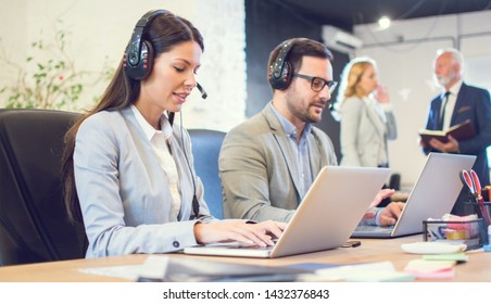 Young business woman with headset using laptop at her workplace in office. Female sales agent talking with client using headphones and microphone and working on laptop.