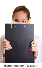Young business woman hiding behind a clipboard