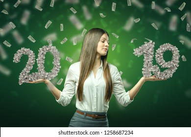 Young business woman holding '20' and '19' dollar signs in her hands with dollars in the air on green background. Business and finance. Banking and financial industry. Management and savings.