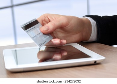 Young business woman  holding  a credit card . On-line shopping on the internet using a tablet