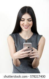Young business woman holding a smart phone in her hands and smiling.