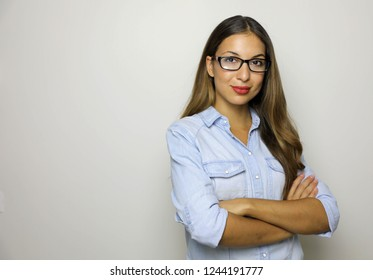 Young business woman in jeans shirt and glasses standing with crossed arms. Isolated studio portrait. Copy space.