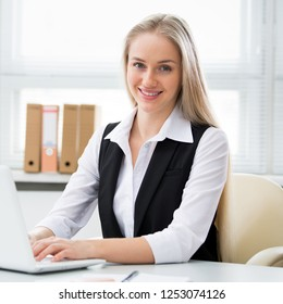 Young business woman with laptop in the office