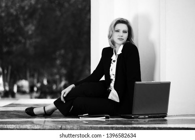 Young business woman with laptop sitting at the wall Stylish fashion model in black suit